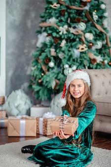 Menina chapéu de papai noel com presentes debaixo da árvore de natal, sentado junto à lareira, descompacta presentes.