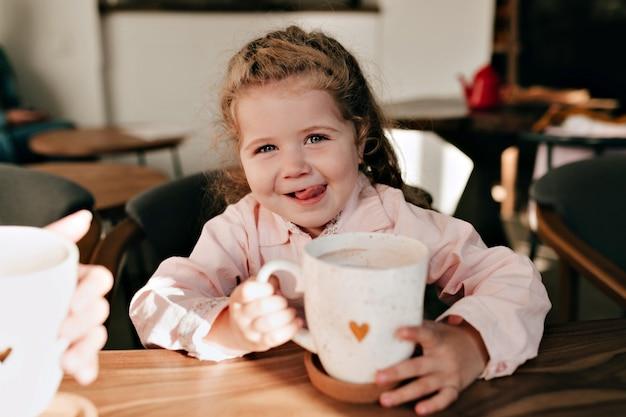 Menina charmosa com cabelos loiros encaracolados se divertindo e bebendo chocolate quente com um sorriso feliz