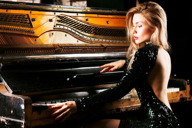 Menina charmosa em um vestido de noite posando perto do antigo piano alemão