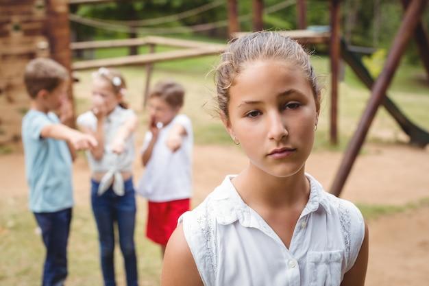 Menina chateada com amigos fofocando no fundo