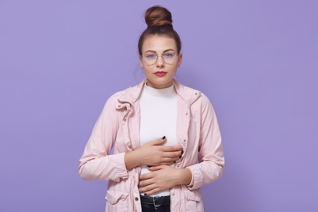 Menina chateada e doente com coque de cabelo vestindo jaqueta rosa pálida, sofrendo de dor de estômago aguda, apendicite, espasmo menstrual, posando com as mãos na barriga contra a parede lilás.