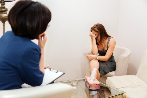 Menina chateada está chorando e chorando. ela está sentada na frente do terapeuta e olhando para baixo. ela está escondendo o rosto. dotor está olhando para a mulher e tentando ouvi-la.