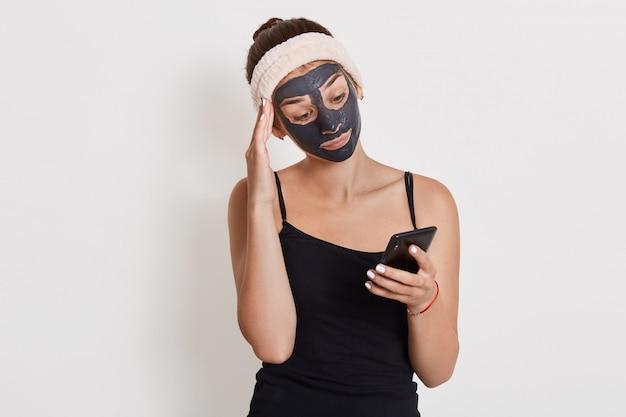 Menina chateada olha para a tela do telefone inteligente e conversando com um amigo, lendo a mensagem com olhar triste, posando de parede branca isolada, mantendo a mão no templo.