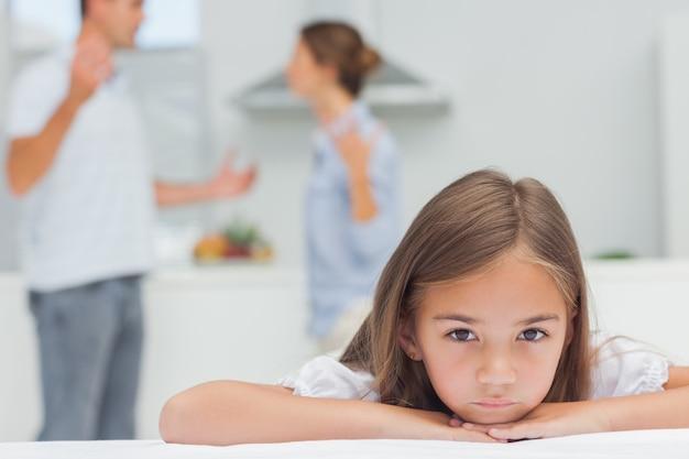 Menina chateada ouvindo os pais brigando