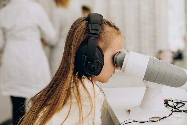 Menina checando a visão no centro de oftalmologia