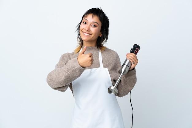 Menina chef usando liquidificador mão sobre branco isolado, dando um polegar para cima gesto