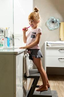 Menina cheia do tiro que escova seus dentes