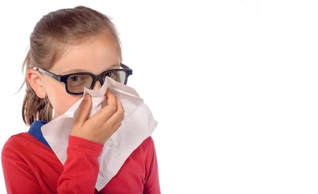 Menina cheira e assoa o nariz com um lenço de papel isolado