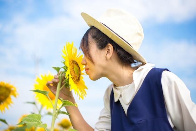 Menina cheira girassol na natureza