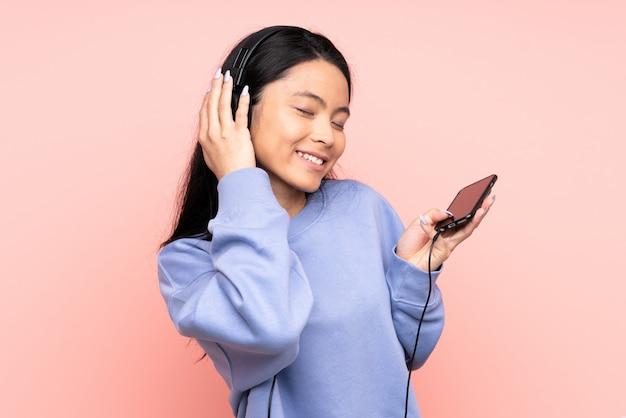 Menina chinesa adolescente isolada em rosa