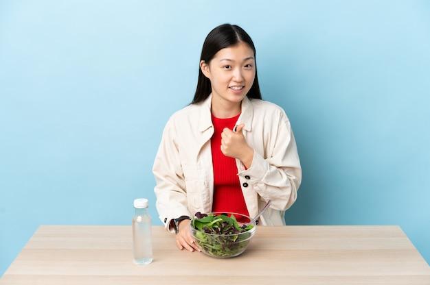 Menina chinesa comendo uma salada fazendo um gesto de polegar para cima