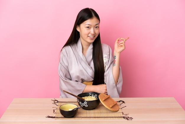 Menina chinesa de quimono comendo macarrão apontando o dedo para o lado