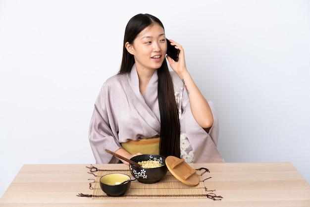 Menina chinesa de quimono, comendo macarrão, conversando com o celular