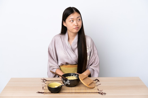 Menina chinesa de quimono comendo macarrão fazendo um gesto de dúvida olhando para o lado