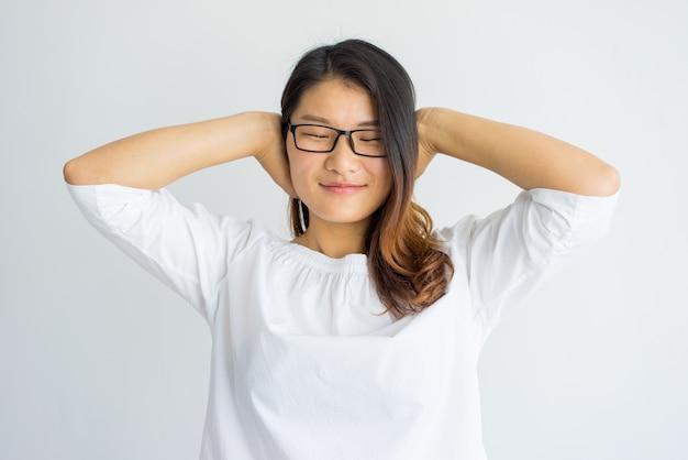 Menina chinesa despreocupada satisfeita que cobre as orelhas com as mãos.