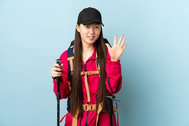 Menina chinesa nova com polos da trouxa e do trekking sobre o azul isolado que conta cinco com dedos