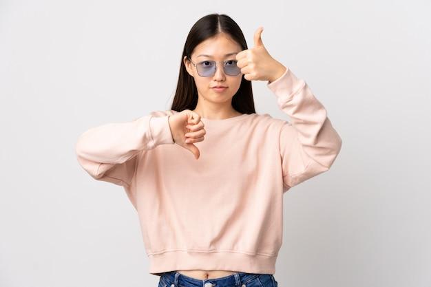 Menina chinesa nova sobre a parede branca isolada que faz o sinal de bom-mau. indeciso entre sim ou não