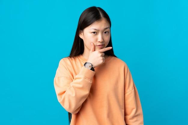 Menina chinesa nova sobre o azul isolado que tem dúvidas