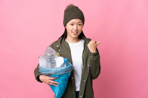 Menina chinesa segurando um saco cheio de garrafas de plástico para reciclar em rosa isolado, apontando para o lado para apresentar um produto