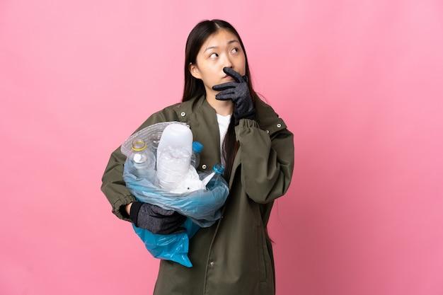 Menina chinesa segurando um saco cheio de garrafas de plástico para reciclar em rosa isolado com dúvidas e com a expressão do rosto confuso