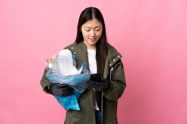 Menina chinesa, segurando um saco cheio de garrafas de plástico para reciclar em rosa isolado, enviando uma mensagem com o celular