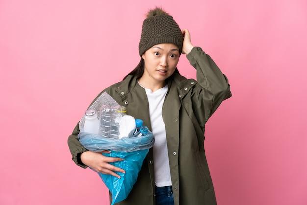 Menina chinesa segurando um saco cheio de garrafas de plástico para reciclar em rosa isolado, fazendo o gesto nervoso