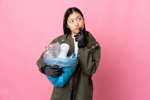 Menina chinesa segurando um saco cheio de garrafas de plástico para reciclar em rosa isolado tendo dúvidas enquanto olha para cima