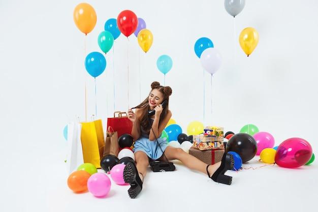 Menina chique, atendendo chamadas de aniversário sentado na sala de estar