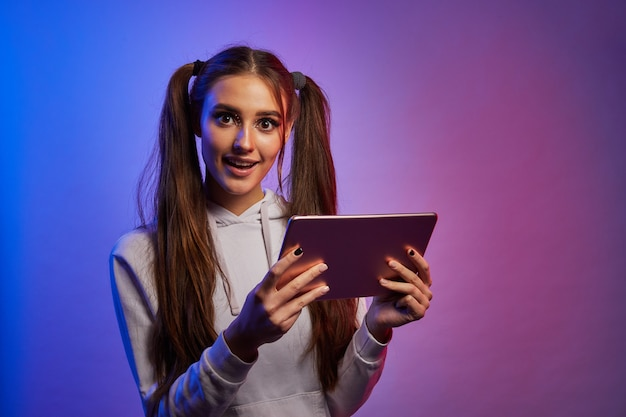 Menina chocada com digital tablet pc, fundo de estúdio de néon. jovem surpreendida com almofada.