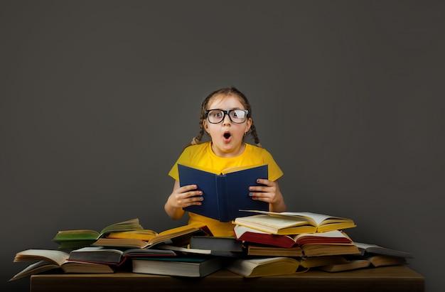 Menina chocada com livros perto de quadro de escola. espaço vazio para texto