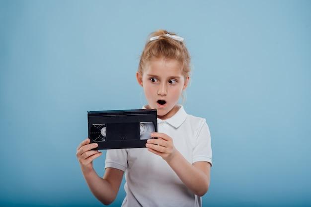 Menina chocada com uma fita de vídeo isolada em um fundo azul de aparelhos antigos