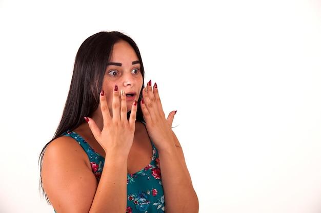Menina chocada e surpresa gritando cobrindo a boca com as mãos