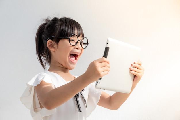 Menina chocada e surpresa na internet com conceito de computador tablet digital para espanto, espanto, cometer um erro, atordoada e sem palavras ou vendo algo que não deveria ver