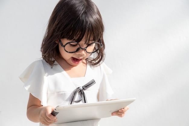 Menina chocada e surpresa na internet com o conceito de computador tablet digital para espanto