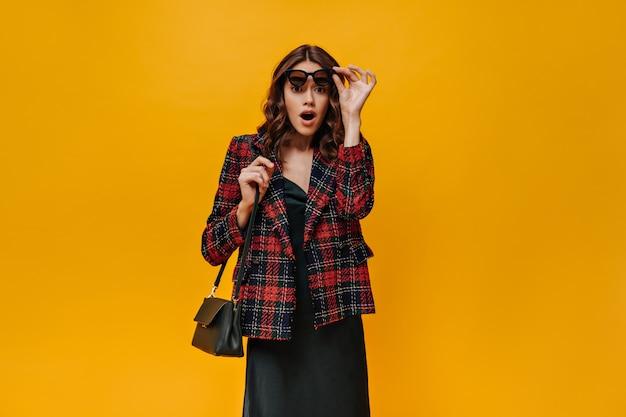 Menina chocada em um vestido preto olhando para a frente em uma parede isolada