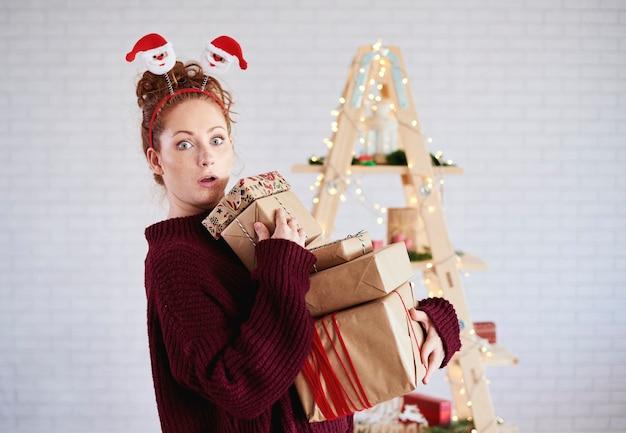 Menina chocada segurando uma pilha de presente de natal