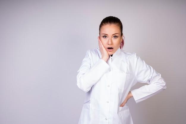 Menina chocante no uniforme branco do doutor