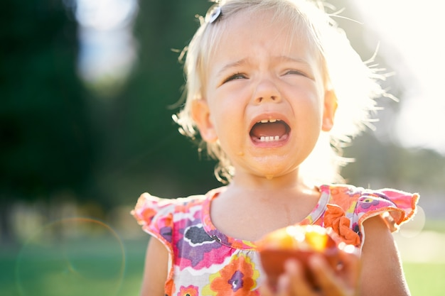 Menina choramingando segurando um pêssego na mão, close up