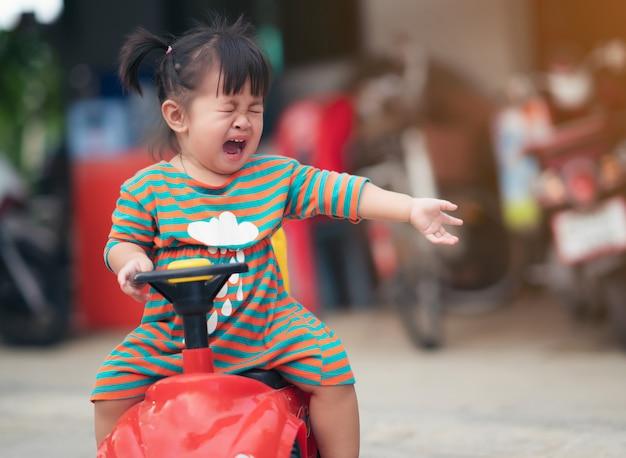 Menina chorando ao ar livre perto do parque infantil