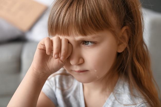 Menina chorando em casa.