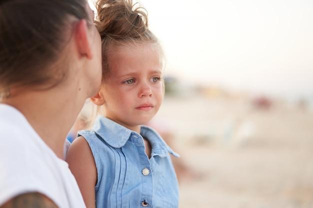 Menina chorando enquanto a mãe beija a testa dela