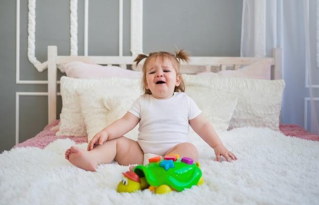 Menina chorando sentada na cama com um brinquedo classificador no quarto