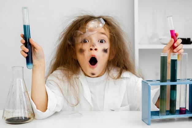 Menina cientista chocada no laboratório com tubos de ensaio e experimento fracassado