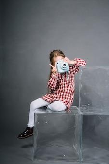 Menina clicando foto da câmera instantânea mostrando sinal de vitória contra o fundo cinza