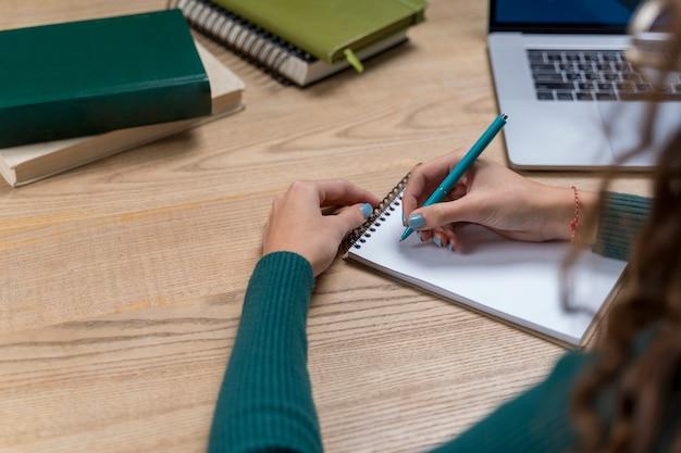 Menina close-up, escrevendo em um caderno