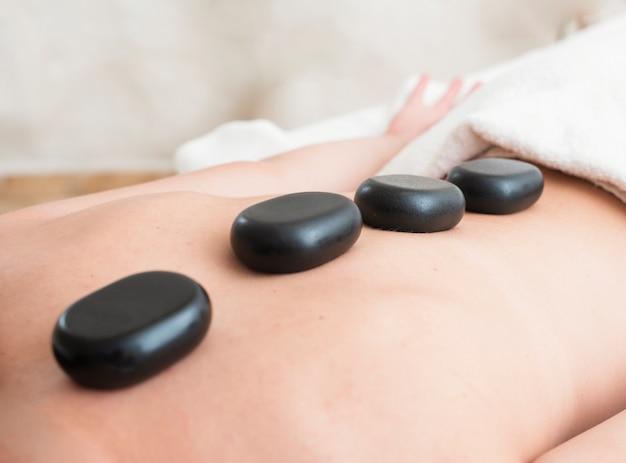 Menina close-up, recebendo um tratamento de spa com pedras
