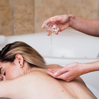 Menina close-up, recebendo uma massagem com óleos