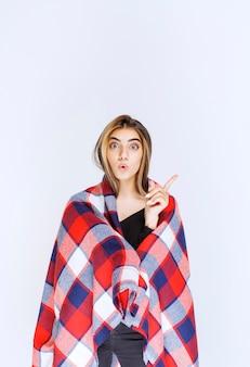 Menina coberta com manta vermelha apontando para algo.