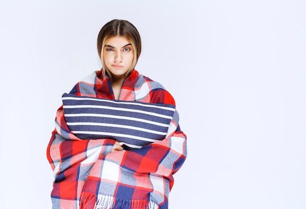 Menina coberta com um cobertor xadrez vermelho e segurando um travesseiro.