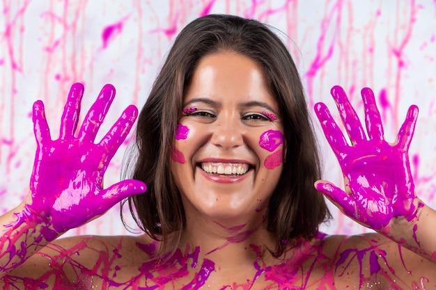 Menina coberta de tinta rosa se divertindo e sendo livre, num conceito que ajuda na conscientização do câncer de mama e na libertação da mulher.
